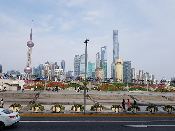 Road and park in the foreground with the Shanghai skyline in the background