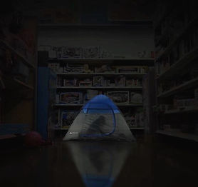 Two kids in a tent inside a department store. Kids inside tent at night.