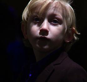 A small boy looks hopeles. Sad Boy wearng suit.