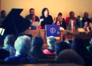 Pastor preaching behind pulpit during Advent worship service