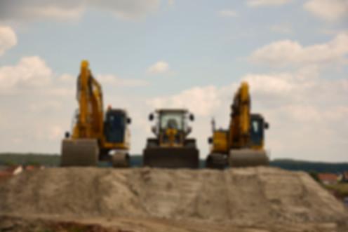 Hinter der Wetteranzeige sieht man einen Radlader auf einem Aushubhügel, der rechts und links von je einem gelben Bagger flankiert wird.
