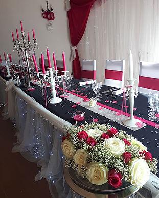 Table de mariage avec une nappe noire et des chases rouges et blanches. Décorations événementielles