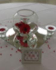 décoration événementielle à louer. Grand bocal avec des fleurs rouges dedans. Le tout posé sur une nappe blanche