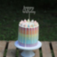 Rainbow cake with ganache drip and topper