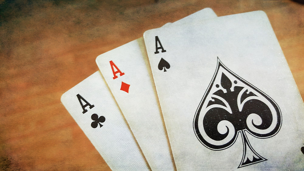 Three playing cards showing Aces