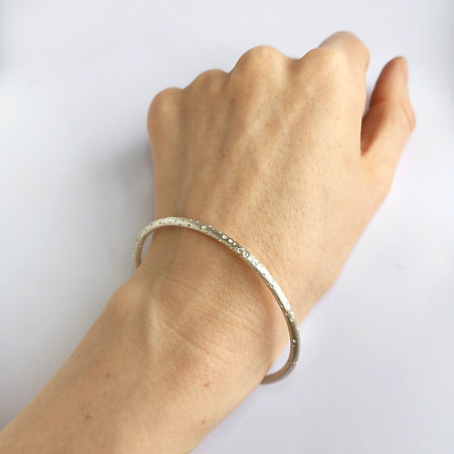Handmade patterned oval silver bangle, created by contemporary jewellery designer Kate Smith. Birmingham Jewellery Quarter