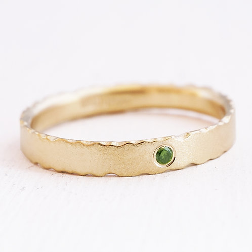 A modern, bespoke handmade engagement or wedding ring with a central, brilliant cut, green diamond. Handmade in Birmingham