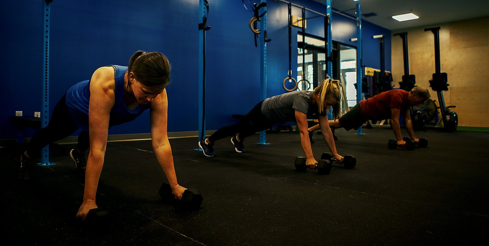 Three people in group class setting, in plank position with dumbbells.