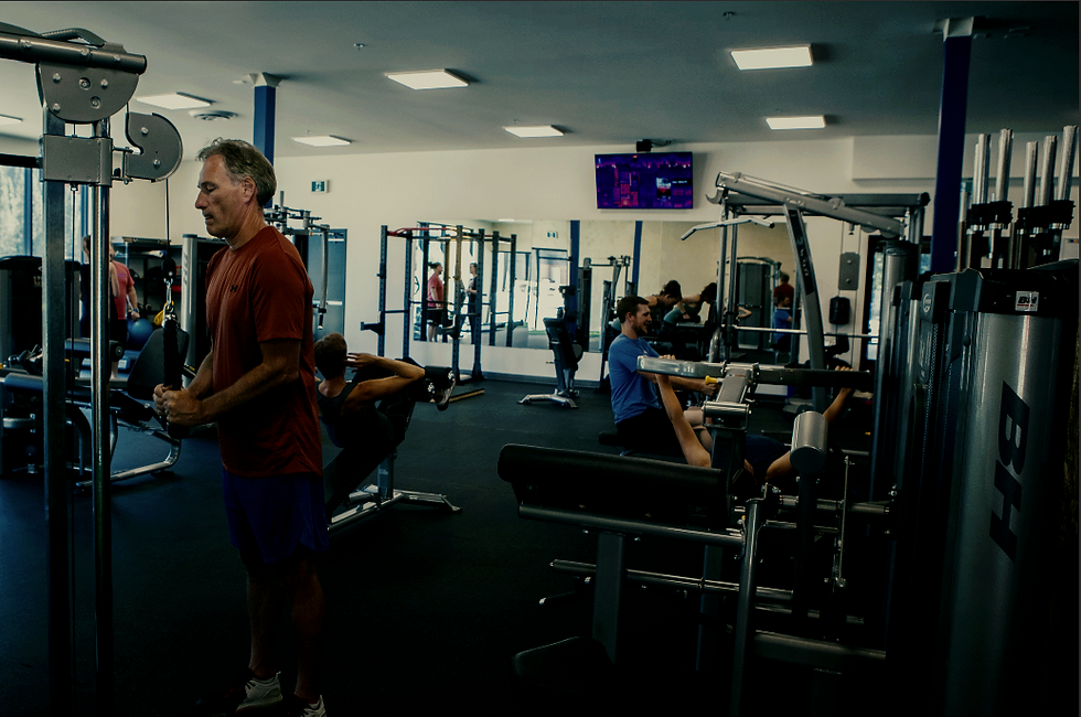 People working out on various gym equpiment, in the open gym.