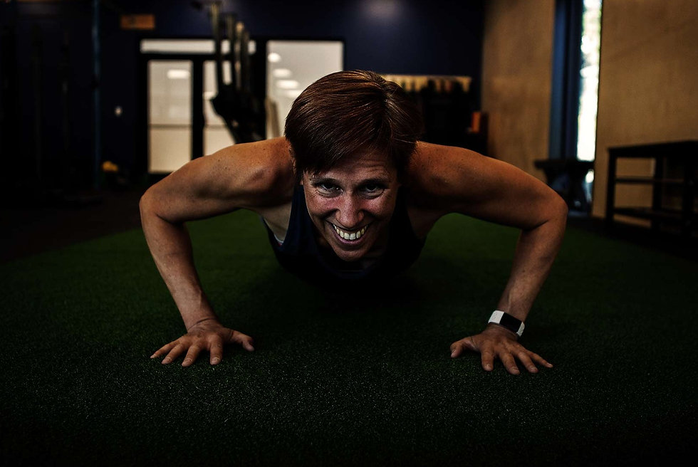 Women smiling doing a push up on green turf.