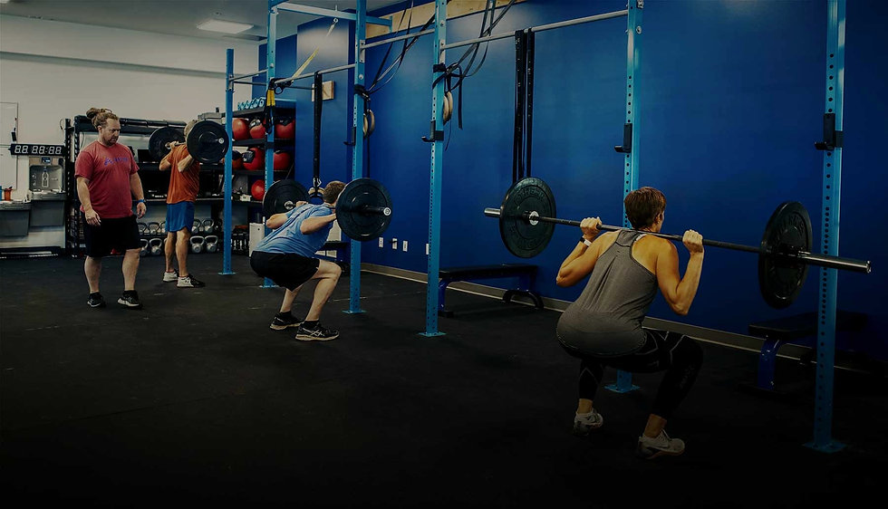 Three people lifting barbells in group class setting with the trainer looking over them.