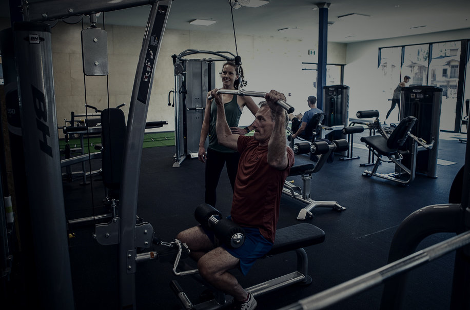 faded picture of women trainer watching man on pull down machine.