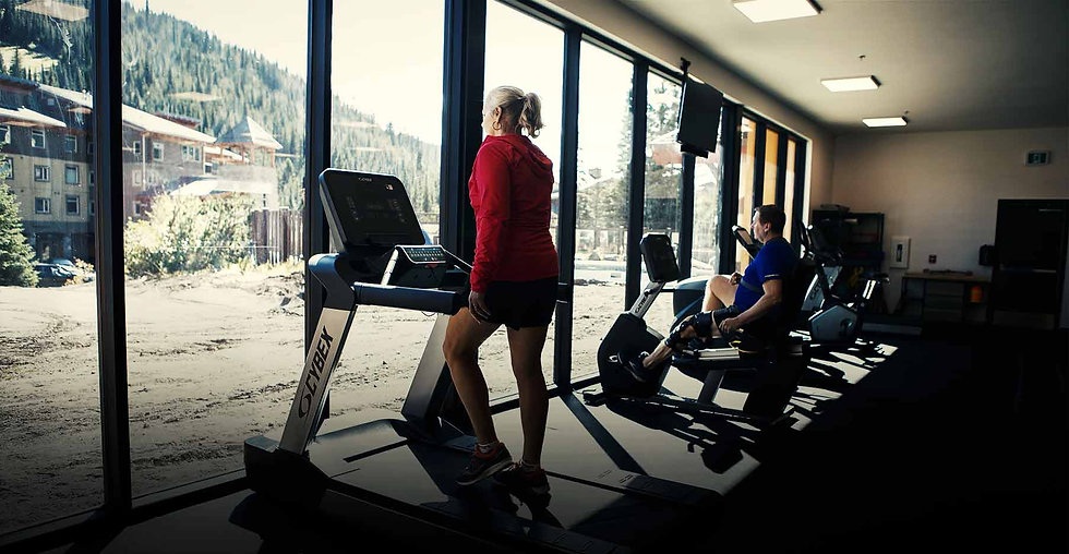 Women on treadmill starring out the window. Man with knee brace on bike in the background.