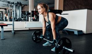 mulher levantando peso academia