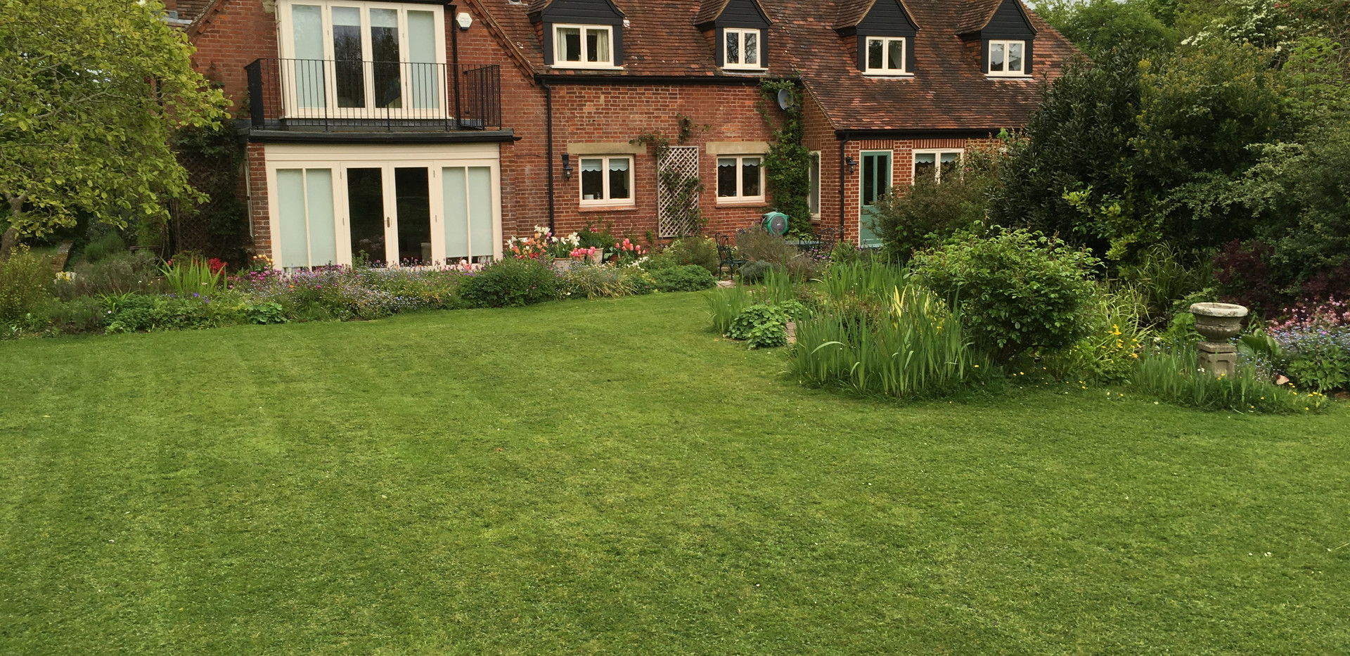 large back garden with mown lawn and tidy beds