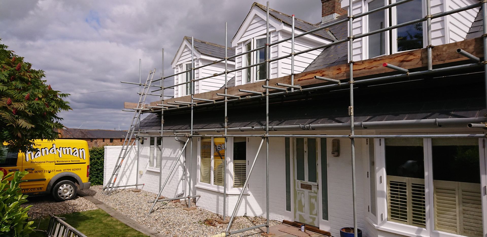 exterior house painting with scaffolding and yellow handyman van