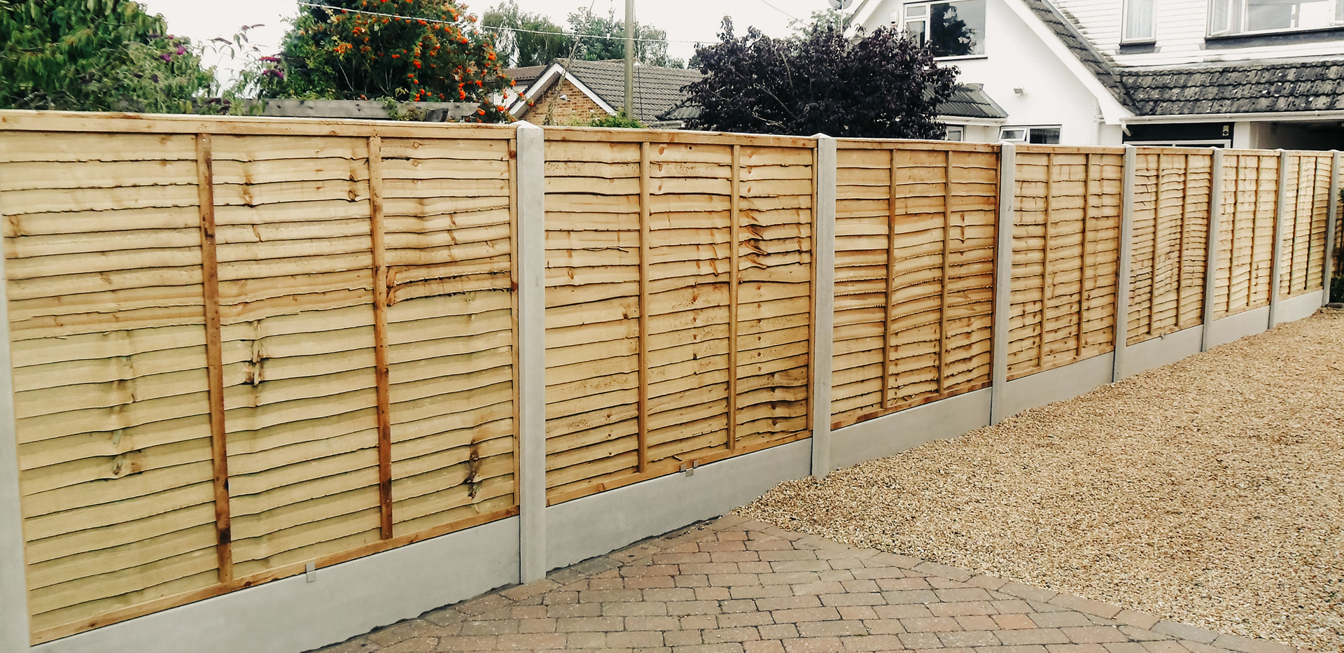 lap panel fencing in front of paved and pebble drive