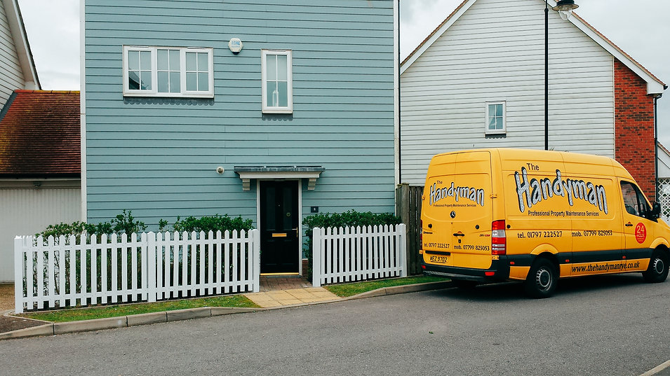 big yellow handyan van in front of house
