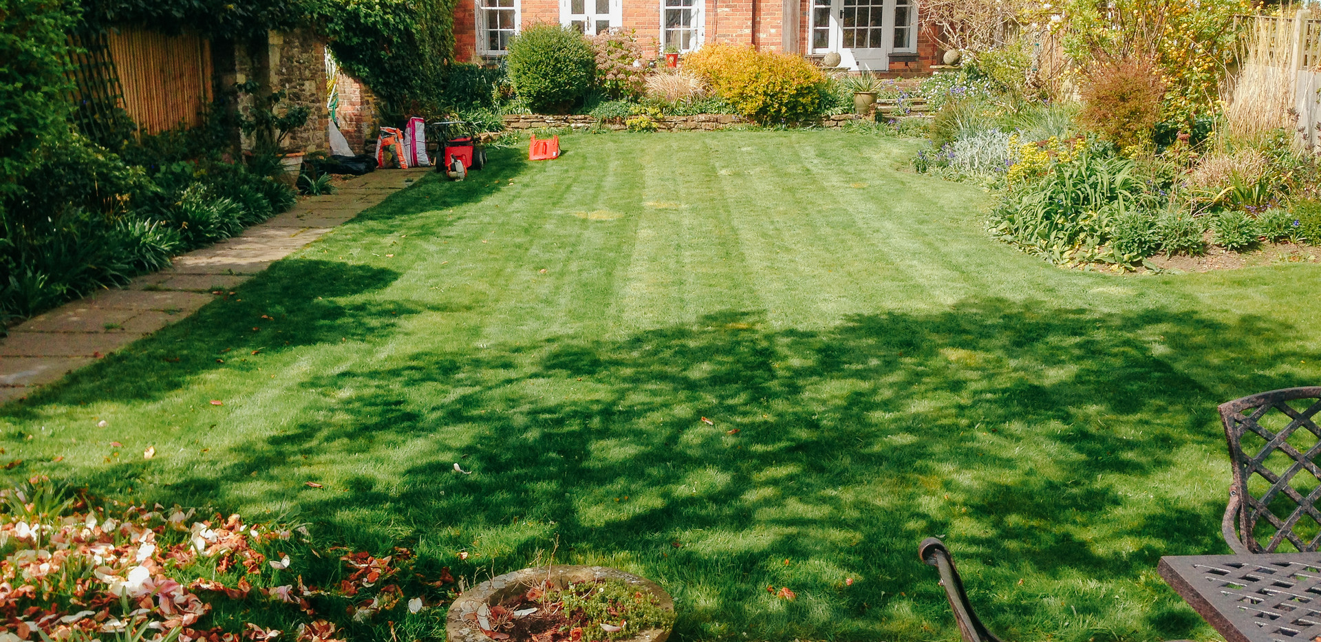 back garden with mown lawn and leaf blower