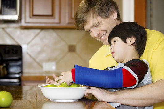 Father helping disabled son putting frui