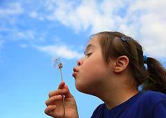 Little girl blowing dandelion on backgro