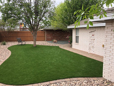 Hardscape design with more artificial turf in the backyard for a no maintenance property.