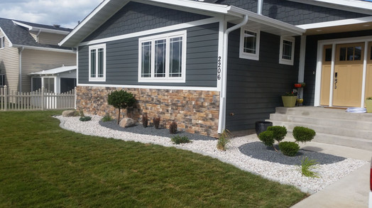 New yard and multicolored rockbeds with plants and shrubs.