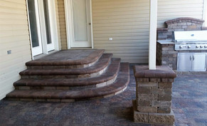 Steps leading to patio and ourtoor kitchen with porcelain countertops.