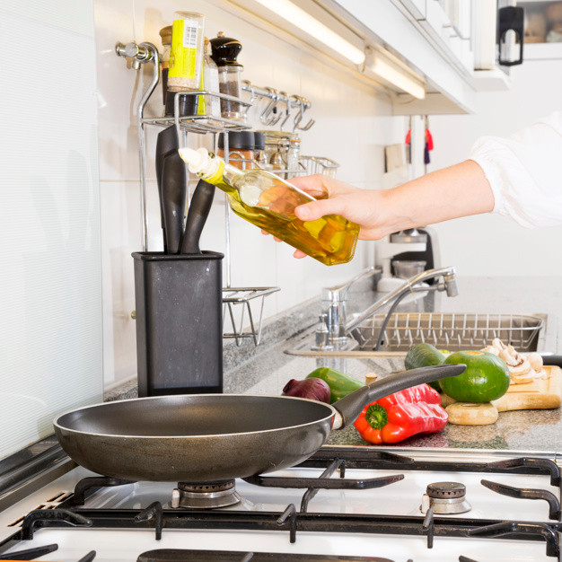 woman-pouring-oil-in-the-frying-pan-over