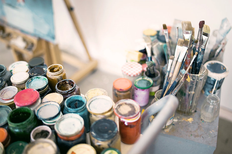 Assorted open jars of paints and brushes