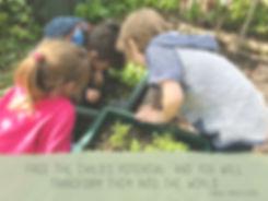 Three children explore a garden bed outside.