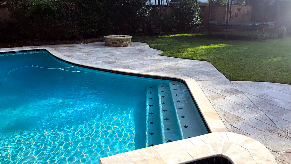 A Stamped Concrete Overlay in this Random Travertine Pattern over this Backyard Poolside Area