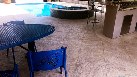 An Outdoor Entertaining Area by the Poolside with a Slate Texture and Custom Scored Pattern Stamped Concrete Overlay