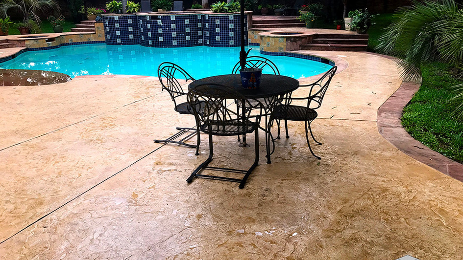 A Stamped Concrete Overlay in a Seamless Slate Texture over this Backyard Outdoor Poolside Area