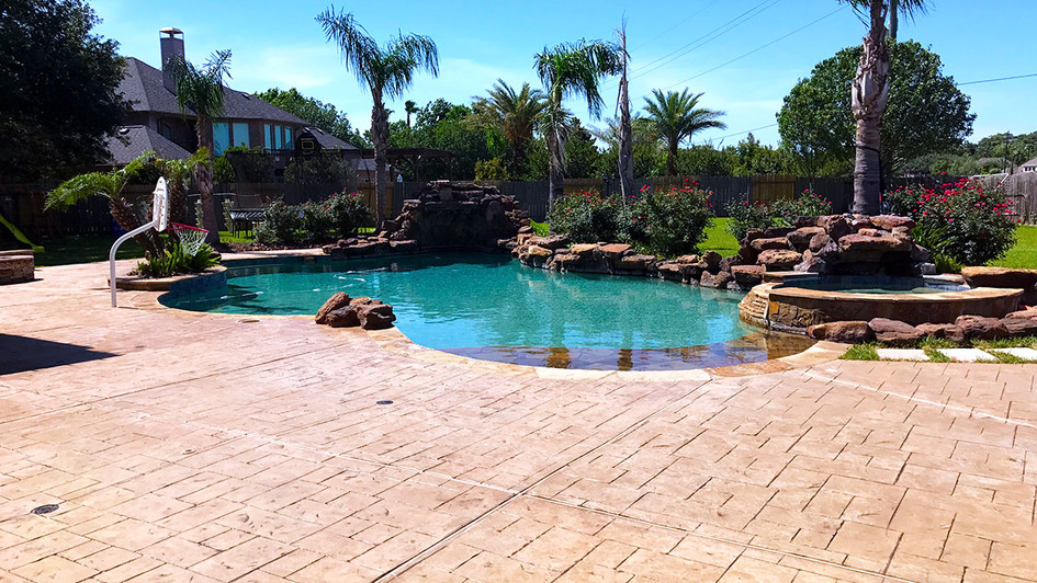 A Fresh Stamped Concrete with a Random Slate Pattern around this Backyard Pool Paradise
