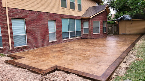 A Blue Stoned Textured Concrete Patio with a Border in a Beautiful Mocha Stained Color