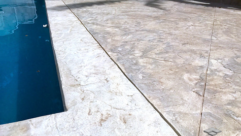 A Stamped Concrete Overlay in a Seamless Slate Texture with a Custom Scored Logo along this Poolside