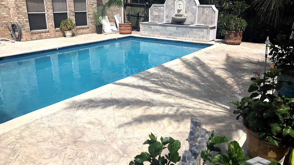 A Stamped Concrete Overlay in a Seamless Slate Texture with Custom Scored Pattern along the Poolside