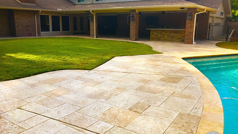 A Stamped Concrete Overlay in a Random Travertine Overlay over this Backyard Poolside Area