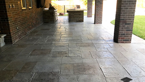 An Outdoor Entertaining Area in a Random Travertine Pattern Stamped Concrete Overlay
