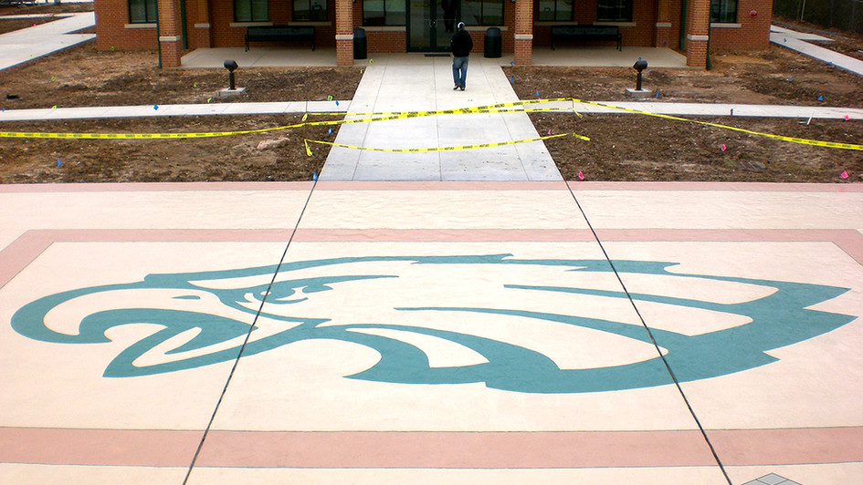 A Custom Scored Logo over Textured Concrete at a High School Athletic Facility