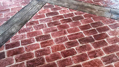 A Red Brick Patio with a Plank Border Stamped Concrete Overlay