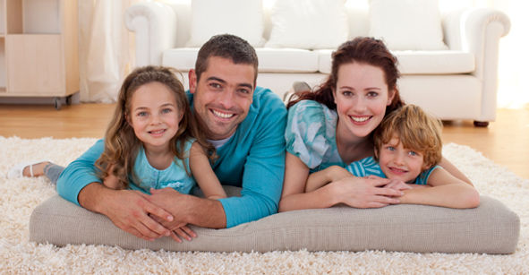 Happy family laying on a freshly cleaned carpet