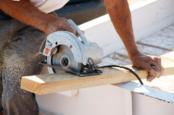 Fence Installer - Sawing a Board