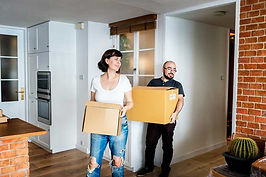 Two people moving boxes into a new home