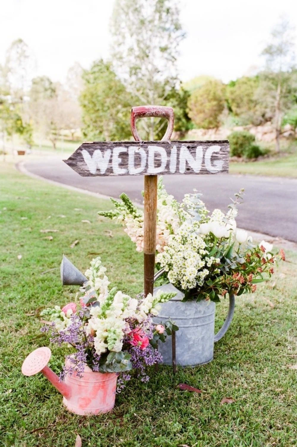 wedding sign with flowers and watering can, show guests to the wedding venue