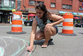 Artist Nicole Kilgore sketches out the design for her roadway mural on Winnisimmet Street.