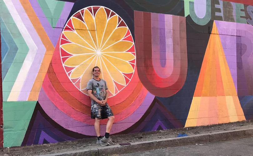"""Alex Cook poses with his mural """"You Are Loved"""""""