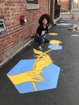 Amber Torres with her work on Division Street