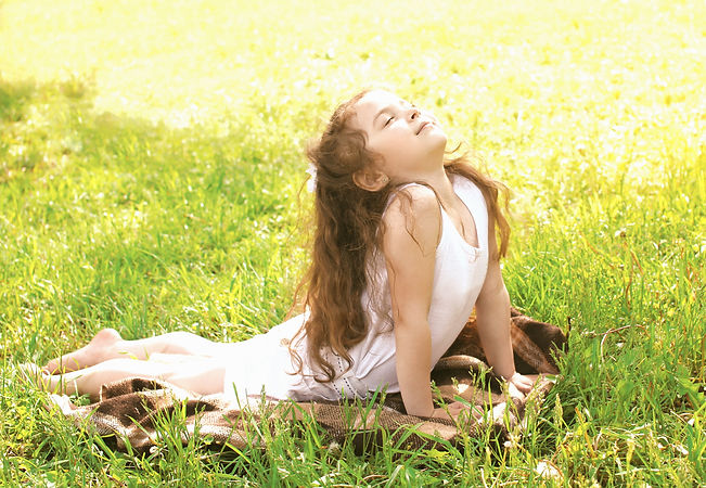 Child doing yoga exercise stretching on grass in sunny summer day_edited.jpg